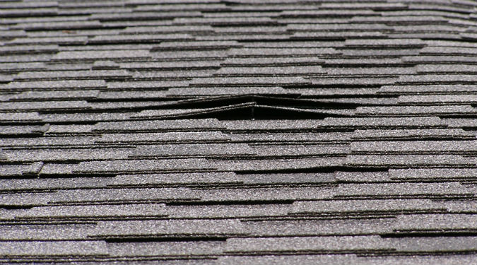 Raised roof shingles caused by raised roofing nail that can lead to roof leaks by Rick Nipper near Raleigh, NC